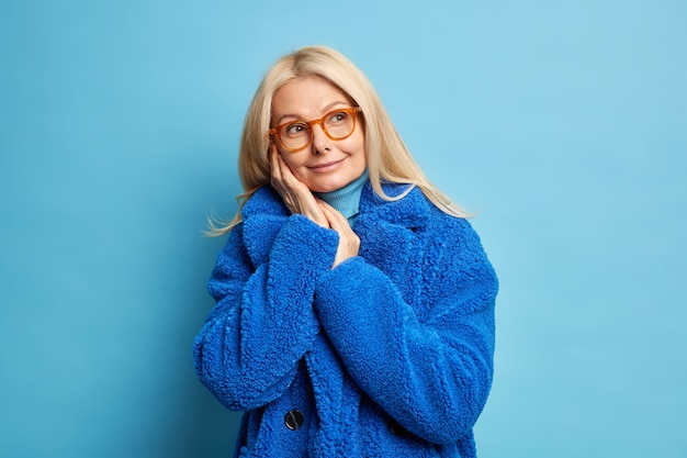 안경을 쓴 중간 나이 든 금발의 여인은 즐거운 일을 회상하며 얼굴 가까이에 손을 유지하면서 미래의 외모에 대해 생각하고 미소를 부드럽게 따뜻한 푸른 겨울 코트를 입습니다.
