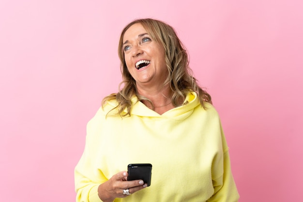 Middle aged blonde woman on isolated pink using mobile phone
