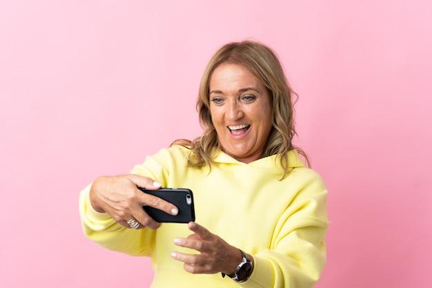 Блондинка средних лет на изолированном розовом играет с мобильным телефоном