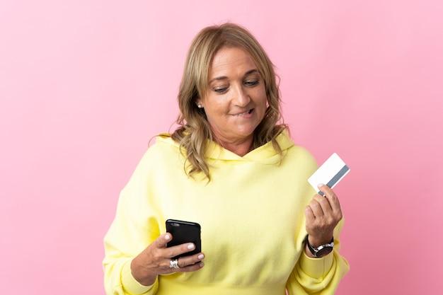 생각하는 동안 신용 카드로 모바일로 구매 격리 된 분홍색 배경 위에 중간 세 금발의 여자