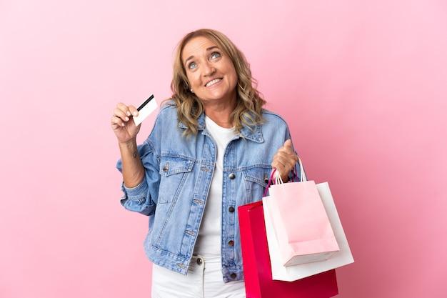 Блондинка средних лет на изолированном розовом фоне держит хозяйственные сумки и кредитную карту