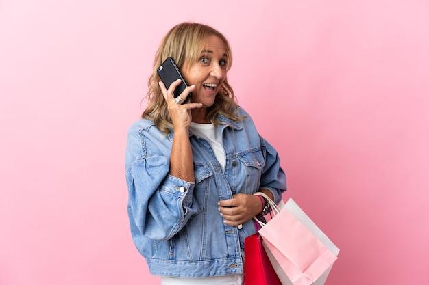 고립된 분홍색 배경 위에 쇼핑백을 들고 휴대전화로 친구에게 전화를 걸고 있는 중년의 금발 여성