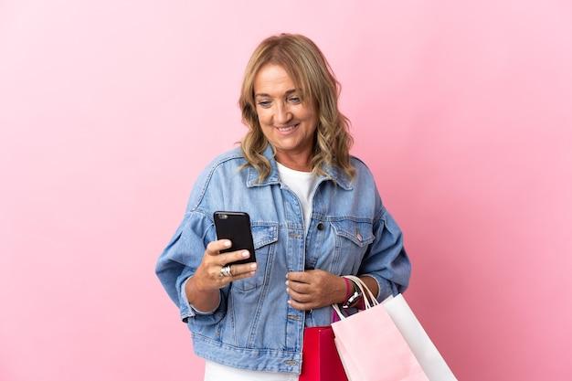 쇼핑 가방을 들고 친구에게 그녀의 휴대 전화로 메시지를 작성하는 격리 된 분홍색 배경 위에 중간 세 금발의 여자