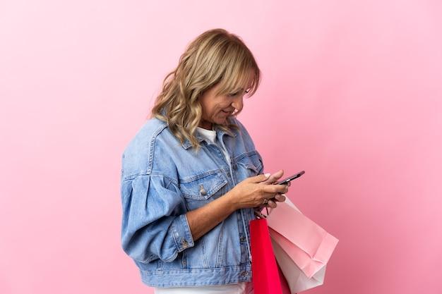 고립된 분홍색 배경 위에 쇼핑백을 들고 휴대전화로 친구에게 메시지를 쓰는 중년의 금발 여성
