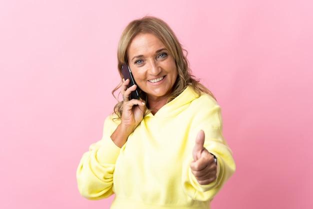 엄지 손가락을하는 동안 모바일과 대화를 유지하는 격리 된 분홍색 배경 위에 중간 세 금발의 여자