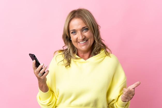 엄지 손가락을하는 동안 휴대 전화를 사용하여 격리 된 분홍색 배경 위에 중간 세 금발의 여자