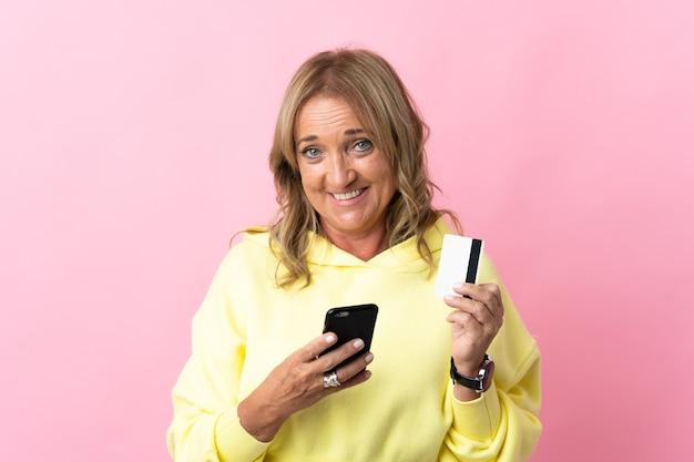 Блондинка средних лет над изолированной розовой покупкой с мобильного телефона с помощью кредитной карты