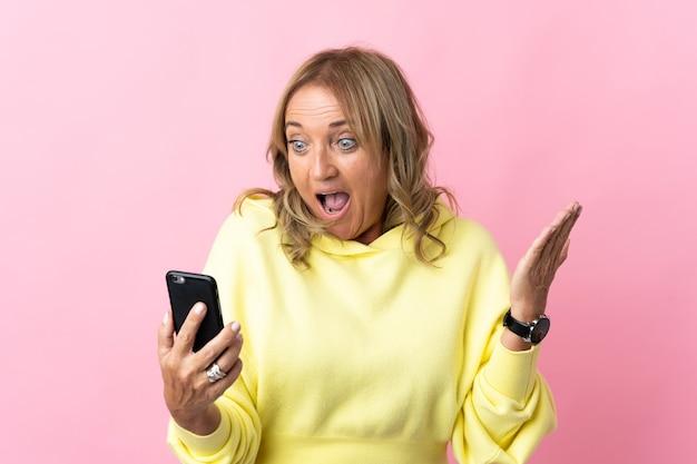 Блондинка средних лет над изолированной розовой смотрит в камеру, используя мобильный телефон с удивленным выражением лица
