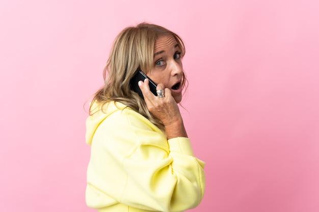 누군가와 휴대 전화로 대화를 유지하는 격리 된 분홍색 벽 위에 중간 세 금발의 여자