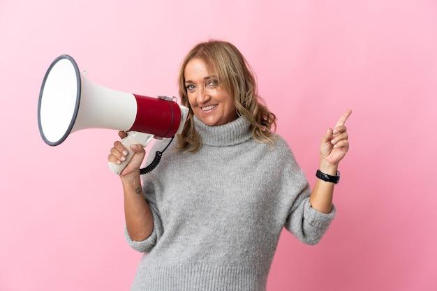 Блондинка средних лет над изолированной розовой стеной кричит в мегафон и указывает сторону