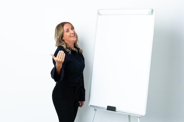 화이트 보드에 프레젠테이션을하고 손으로 초대 고립 된 흰색 배경 위에 중간 세 금발의 여자 프리미엄 사진