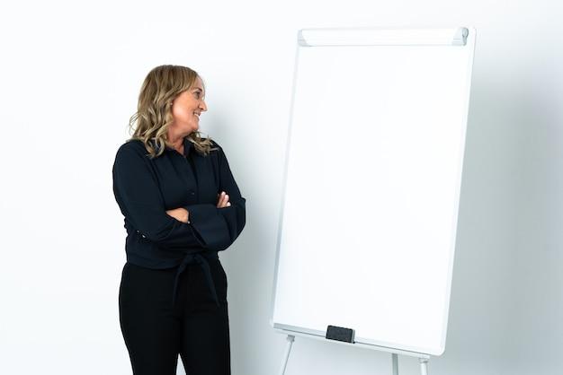 화이트 보드에 프레젠테이션을하고 측면을 찾고 격리 된 흰색 배경 위에 중간 세 금발의 여자