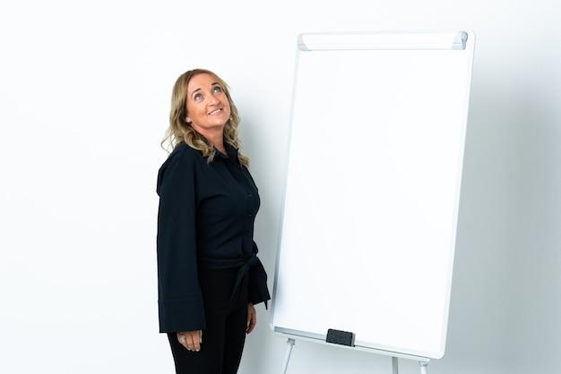 화이트 보드에 프레젠테이션을하고 웃는 동안 찾고 격리 된 흰색 배경 위에 중간 세 금발의 여자
