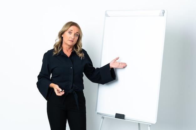 화이트 보드에 프레젠테이션을하고 그것을 가리키는 격리 된 흰색 배경 위에 중간 세 금발의 여자 프리미엄 사진