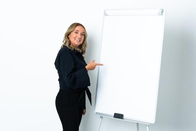 화이트 보드에 프레젠테이션을하고 측면을 가리키는 격리 된 흰색 배경 위에 중간 세 금발의 여자