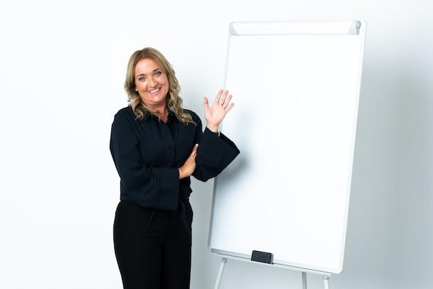 화이트 보드에 프레젠테이션을하고 손으로 경례 격리 된 흰색 배경 위에 중간 세 금발의 여자 프리미엄 사진