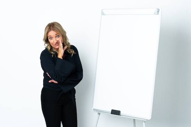 화이트 보드에 프레젠테이션을하고 뭔가 속삭이는 격리 된 흰색 배경 위에 중간 세 금발의 여자