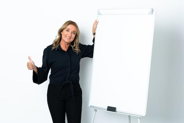 엄지 손가락으로 화이트 보드에 프레젠테이션을 격리 된 흰색 배경 위에 중간 세 금발의 여자