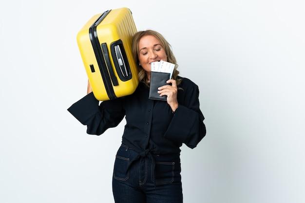 여행 가방과 여권으로 휴가에 고립 된 흰색 배경 위에 중년 금발 여자