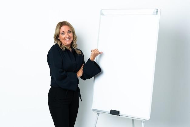 Блондинка средних лет над изолированной белой стеной делает презентацию на белой доске и указывает в сторону
