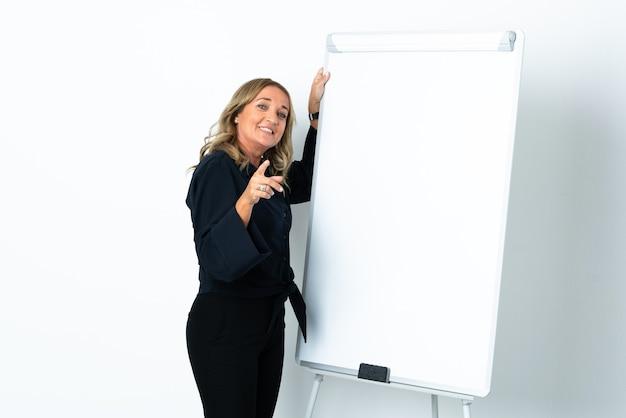 화이트 보드에 프레젠테이션을 격리 된 흰 벽 위에 중간 세 금발의 여자