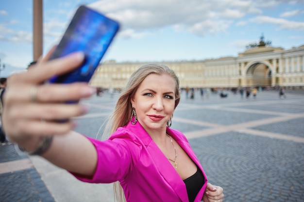 Middle-aged blonde woman in pink suit is taking selfie by mobile phone in historic center of saint-petersburg, russia.