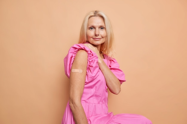 中年の金髪の女性は、絆創膏で腕がコロナウイルスに対する接種を受けることを示し、パンデミックの発生時に彼女の健康を保護しますピンクのドレスを着てベージュのスタジオの壁に座っています