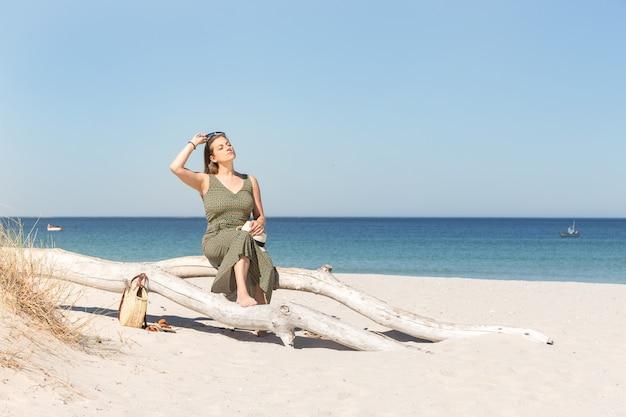 Блондинка средних лет сидит на стволе дерева с видом на море и пляж на спине