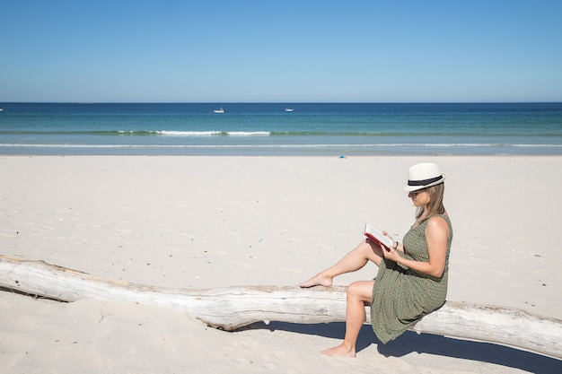 Middle-aged blonde woman sitting on a tree trunk in the beach reading a book