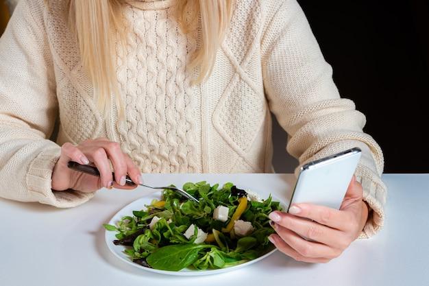 キッチンでサラダを食べながらスマートフォンを使用する中年金髪女性、ライフスタイルのコンセプト、クローズアップ