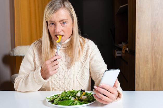キッチンでサラダを食べながらスマートフォンを使用する中年金髪女性、ライフスタイルコンセプト