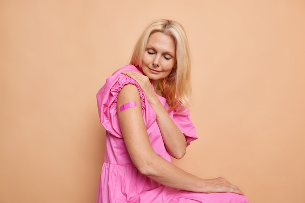 Middle aged blonde woman wears aid band on shoulder after getting vaccine shot shows vaccinated arm wears pink dress