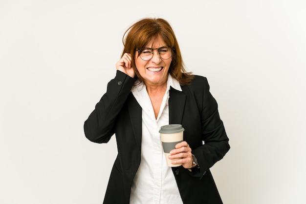 테이크 아웃 커피를 들고 중간 나이 든된 비즈니스 여자 손으로 귀를 덮고 격리.