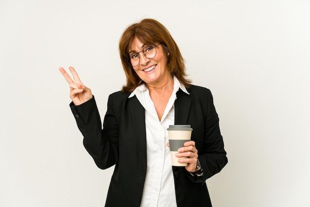 테이크 아웃 커피를 들고 중간 나이 든된 비즈니스 여자 손가락으로 평화의 상징을 보여주는 즐겁고 평온한 고립.