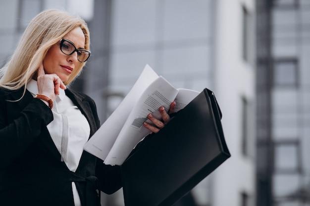 Деловая женщина средних лет держит документы в бизнес-центре