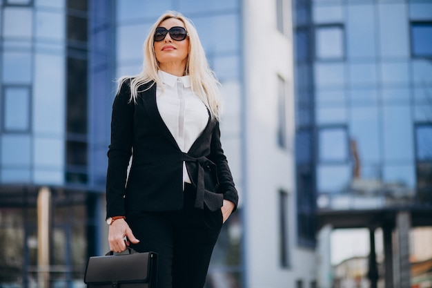Деловая женщина средних лет с чемоданом в деловом центре
