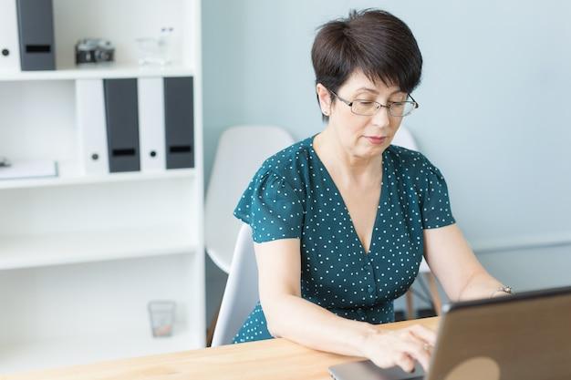 그녀의 사무실에서 노트북에서 일하는 중간 나이 든된 비즈니스 우먼