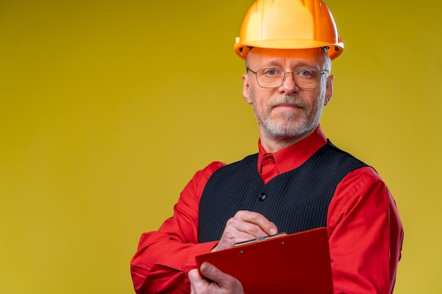 Middle aged businessman in helmet standing and holding file folder. horizontal format isolated on yellow background.