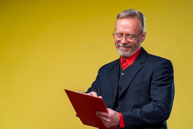 Middle aged businessman holding file folder. horizontal format isolated on yellow background.