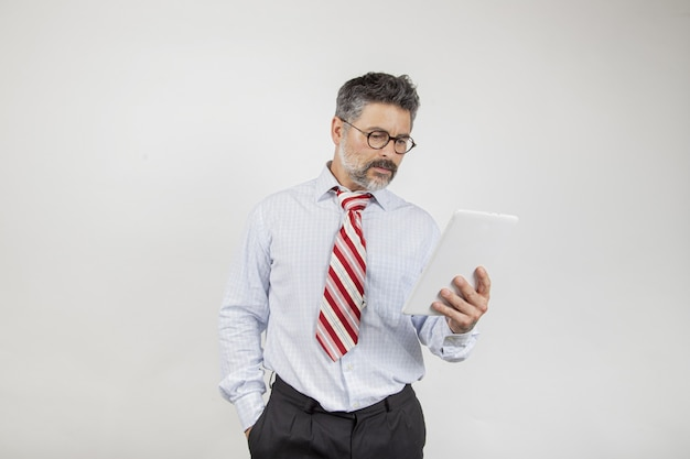 Middle-aged businessman looking at the screen on white background
