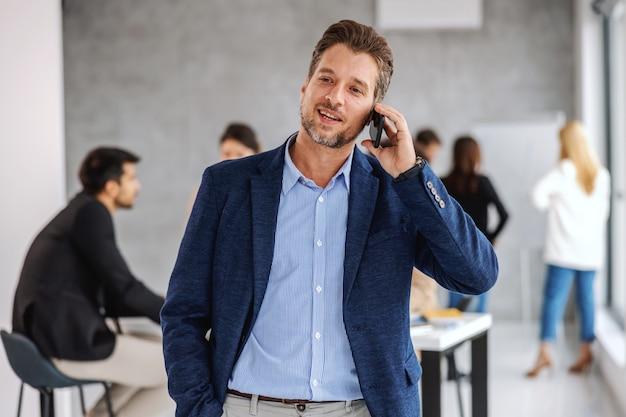 重要な会議中に会議室に立って鋭い服を着た中年のビジネスマン