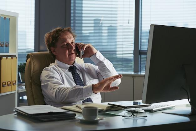 Среднего возраста бизнесмен разговаривает по телефону и жесты