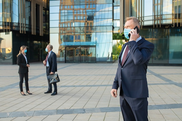 Middle aged businessman wearing mask and office suit talking on mobile phone outdoors. businesspeople and city building glass facade in background. copy space. business and epidemic concept