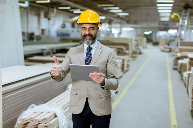 Middle-aged businessman with digital tablet in factory