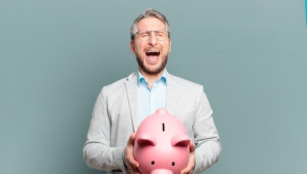 お金と貯金箱を持つ中年のビジネスマン