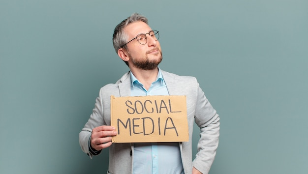 Middle aged businessman with social media board