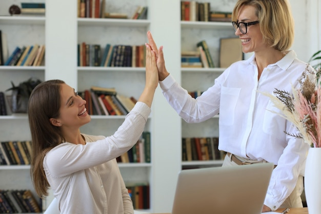 Деловая женщина средних лет, давая высокую пятерку своему молодому коллеге-женщине.