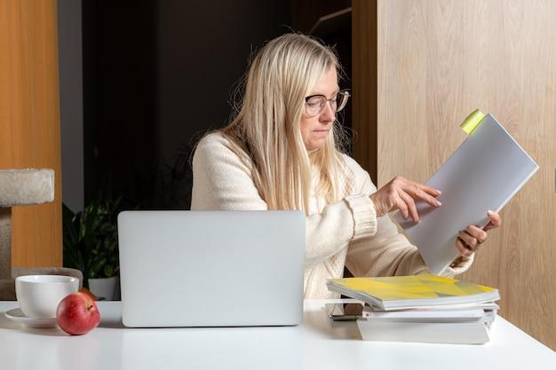 Деловая женщина средних лет сидит за столом, работая с документами и ноутбуком из домашнего офиса