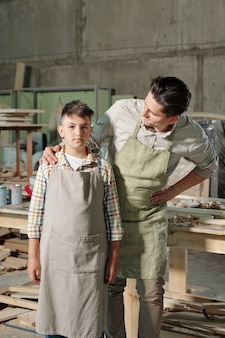 Middle-aged carpenter in apron touching shoulder of son while supporting him in workshop