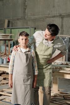 ワークショップで彼をサポートしながら息子の肩に触れるエプロンの中年大工